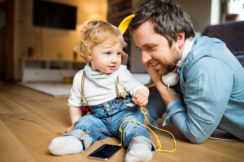 young farther and his little son with smart phone and earphones at home sitting on the floor whilst trying to work from home